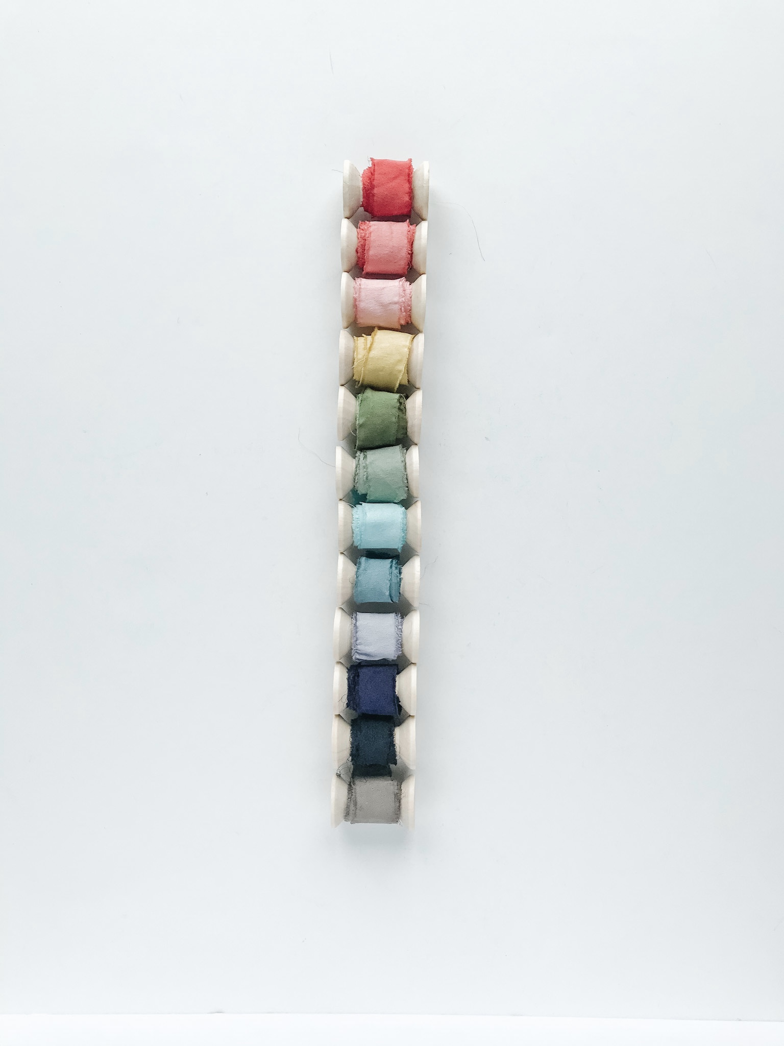 "rainbow of raw edge 1"" hand dyed silk ribbon on wooden spools"